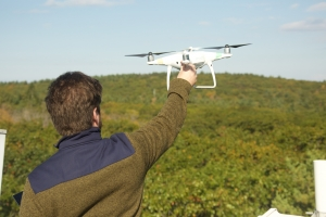 David Basler launches a research drone from the top of a canopy research tower at Harvard Forest. Photo by David Foster.