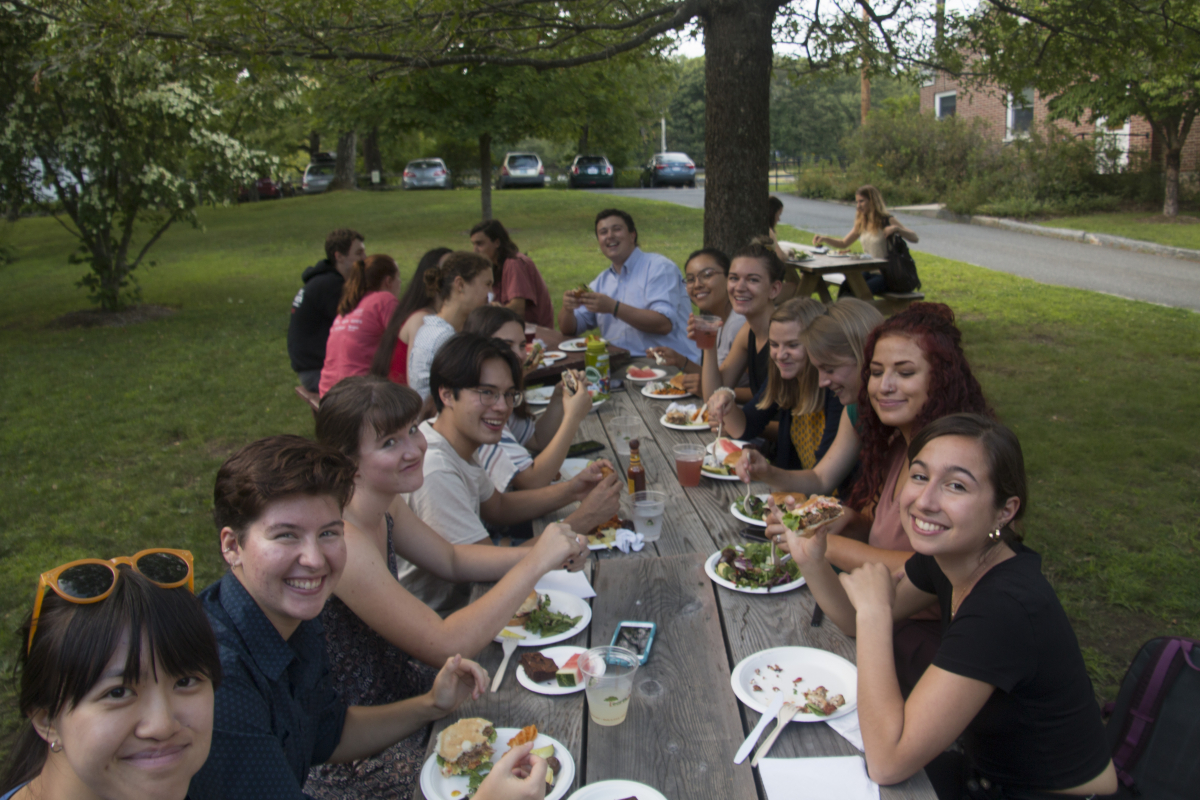 a group of 20 summer students sits at tables eating lunch