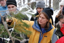 Missy Holbrook shows students a white pine tree in the forest in winter