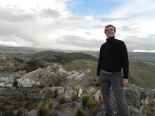 Bullard Fellow Robin Sears stands on a mountaintop in southern Peru, with rocks in the foreground and grass and forest-covered mountains in the distance