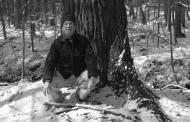 David Kittredge kneeling in front of a tree.