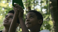 Two middle school students stand in a forest measuring the height of a tree