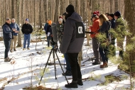 A dozen Harvard Forest scientists and a film crew stand in the snowy woods