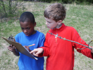 Two children looking at a clipboard and holding a stick.