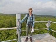 Alison Ochs standing above the canopy on the Hemlock Tower