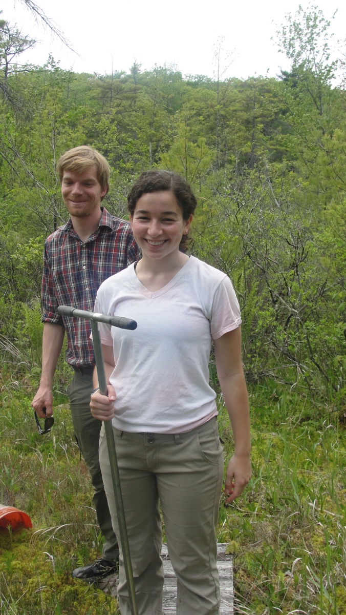 Megan Wilcots and Marco Keiluweit standing on a boardwalk in a wetland. Megan is holding a soil corer.